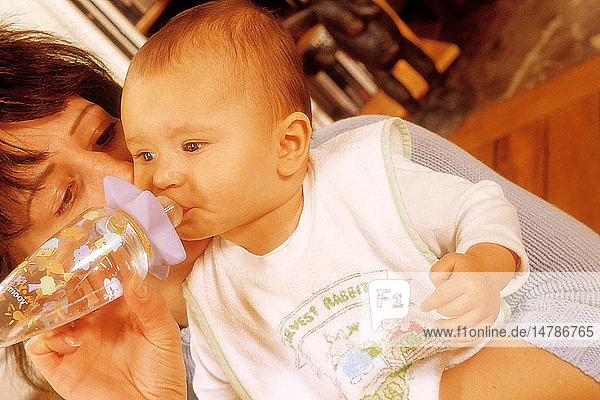INFANT DRINKING FROM BABY BOTTLE