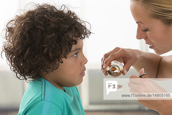 Mother giving her son a spoon of medicine.