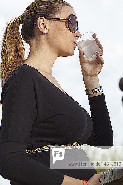 Pregnant woman drinking water.
