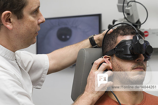 Reportage on an ENT doctor in Nice  France  treating patients suffering from dizziness. A 37-year old patient during a vibration test. During the test  a source of vibration is applied behind the ear on the skull to analyse the consequences on the stability of eye movement (nystagmus).