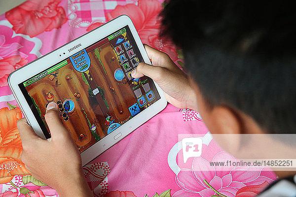 Boy playing on digital tablet.