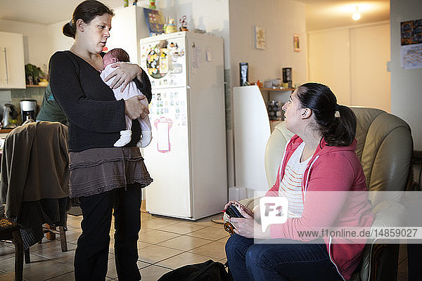 Reportage on an independent midwife during post-partum home visits. The midwife gives advice to the new parents.