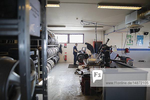 Man balancing the wheel in garage