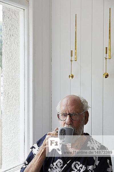 Senior man drinking from mug