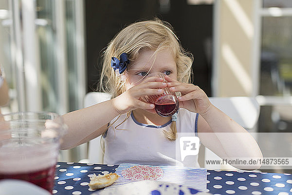 Girl drinking at table