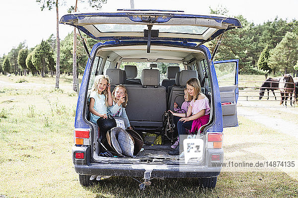 Children sitting in car trunk