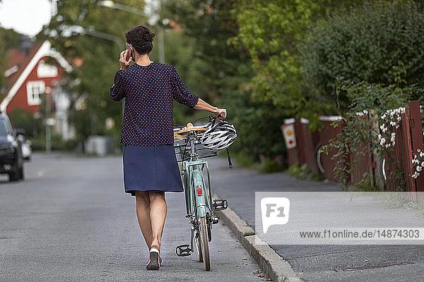 Woman pushing bike along road