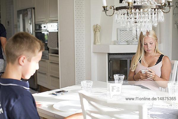 Kinder am Tisch benutzen ein Mobiltelefon