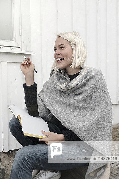 Young woman sitting on stairs with notebook