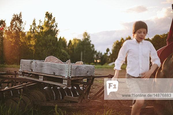 Boy standing near plow