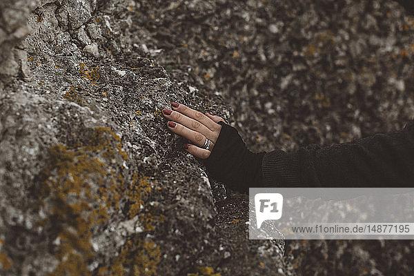 Female hand touching rocks
