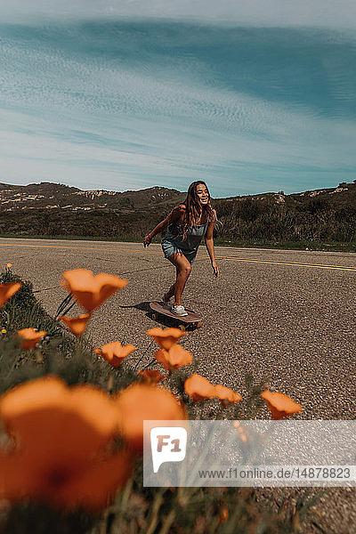 Junge Skateboarderin beim Skateboarden entlang einer Landstraße  Jalama  Kalifornien  USA