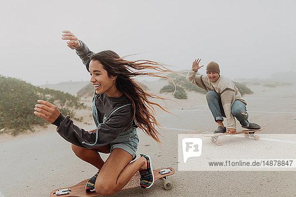 Junges Paar fährt Skateboard auf einem Parkplatz am nebligen Strand  Jalama  Kalifornien  USA