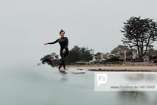 Junges Surferpaar beim Surfen auf nebliger See  Ventura  Kalifornien  USA
