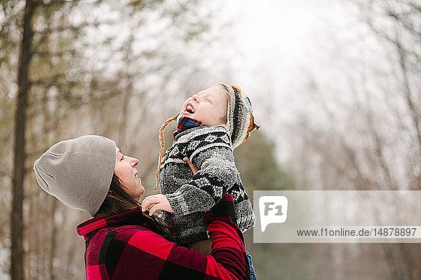 Mutter trägt Sohn im Wald hoch