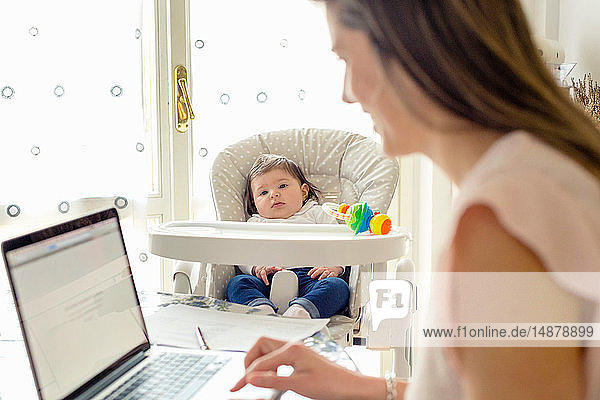 Baby girl watching mother working on laptop at home