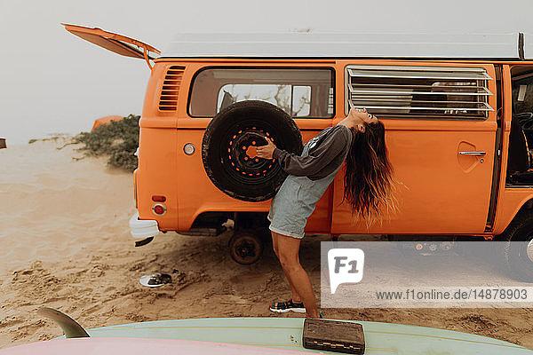 Junge Frau hält Reifen eines Wohnmobils am Strand hoch  Jalama  Kalifornien  USA