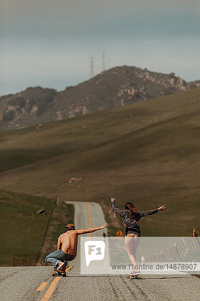 Junges Skateboardfahrerpaar beim Skateboarden auf der Landstrasse  Rückansicht  Jalama  Kalifornien  USA