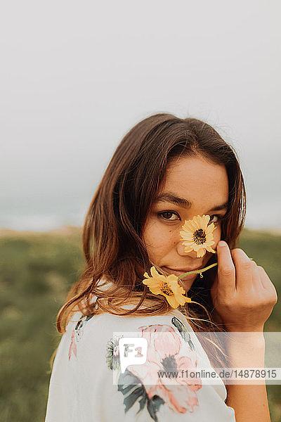 Junge Frau hält an der Küste Wildblumen vor dem Gesicht  Porträt  Jalama  Kalifornien  USA