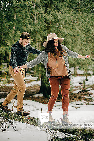 Couple balancing on fallen tree trunk in forest  Tobermory  Canada