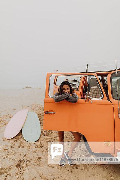 Junge Frau  die sich am Fenster eines Wohnmobils am Strand anlehnt  Porträt  Jalama  Kalifornien  USA