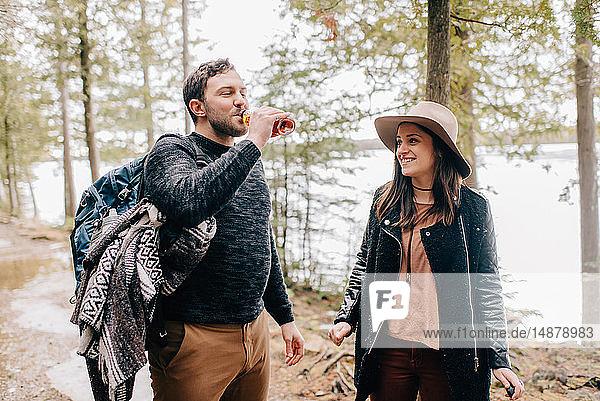 Ehepaar löscht Durst während einer Wanderung im Wald,  Tobermory,  Kanada