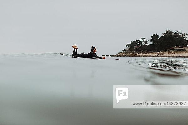 Junge Surferin liegt auf einem Surfbrett in nebliger ruhiger See  Ventura  Kalifornien  USA