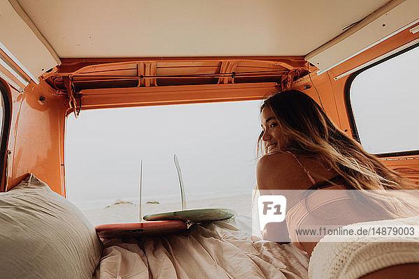 Junge Surferin im Bikini auf dem Rücksitz eines Wohnmobils am Strand liegend  Jalama  Kalifornien  USA