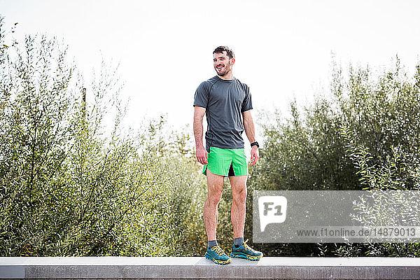 Junger männlicher Läufer steht lächelnd an der Wand