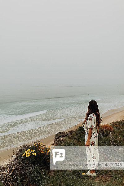 Junge Frau blickt von Klippe auf nebliges Meer  Jalama  Kalifornien  USA