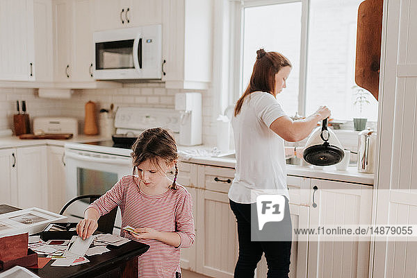 Girl arranging cards in kitchen  mother pouring hot water in background