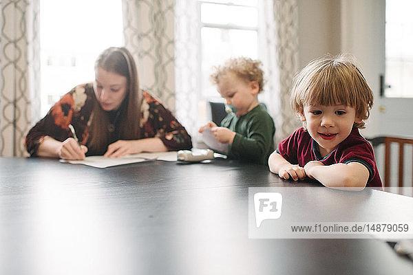 Mutter füllt Formular aus  während die Söhne am Tisch spielen
