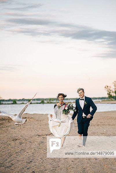 Romantic bride and groom running barefoot on lakeside  Lake Ontario  Toronto  Canada