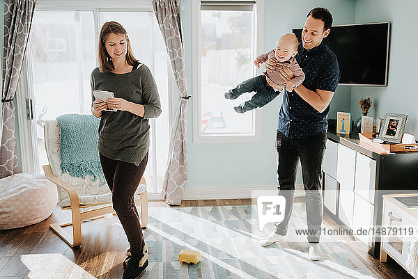 Mid adult couple playing with baby son in living room