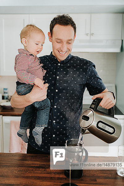Father carrying baby son making coffee at kitchen counter