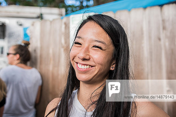 Smiling woman by wooden fence  Haleiwa  Oahu  Hawaii