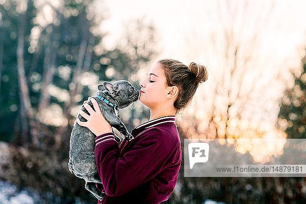 Mädchen küsst französischen Bulldoggenwelpen im Freien
