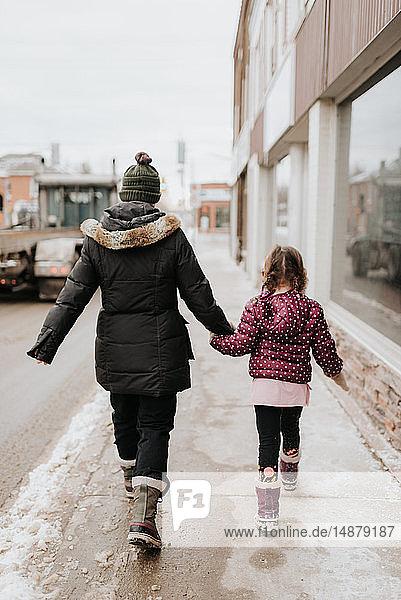 Mutter und Tochter gehen im Winter am Geschäft vorbei