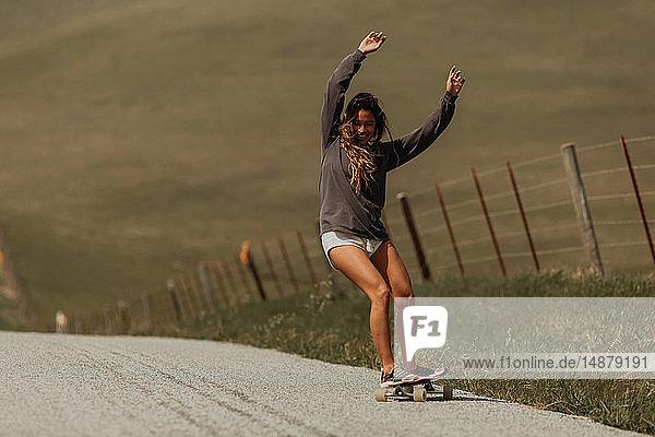 Junge Skateboarderin beim Skateboarden auf der Landstrasse  Jalama  Kalifornien  USA