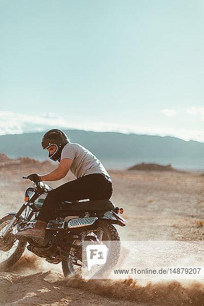 Motorcyclist enjoying stunts  Trona Pinnacles  California  US