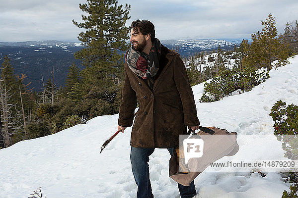 Mid adult man carrying logs and axe on snow covered mountain  Twain Harte  California  USA