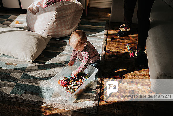 Baby boy sitting on living room floor playing with toys