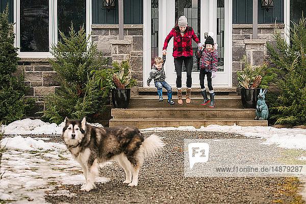 Familie mit Haushund verlässt das Haus  um auszugehen