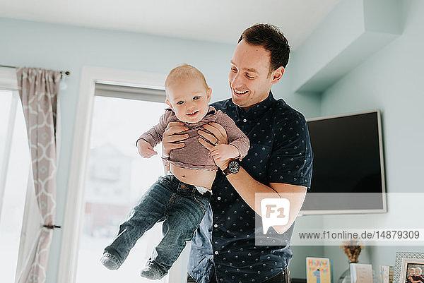 Vater spielt mit dem kleinen Sohn im Wohnzimmer