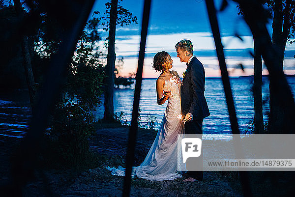 Bride and groom with sparklers by lakeside at dusk  Lake Ontario  Toronto  Canada