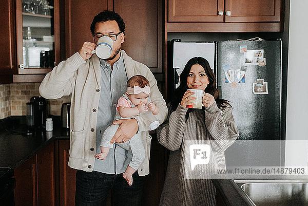 Ehepaar trinkt und trägt Tochter in der Küche