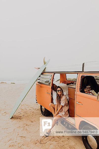 Junge Surferin sitzt auf einem Wohnmobil am Strand  Portrait  Jalama  Ventura  Kalifornien  USA