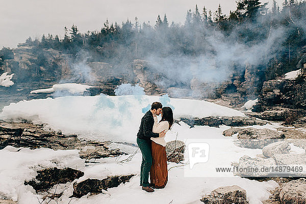 Couple kissing in snow and rock landscape  Tobermory  Canada
