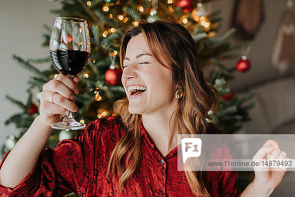 Woman dancing with wine beside decorated Christmas tree