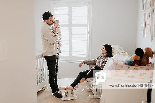 Paar mit Baby-Tochter im Babyzimmer